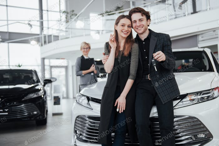 Two happy young attractive owners of car, elegant salesperson at background