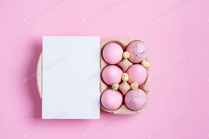 Paper container of craft pink painted Easter eggs and sheet of paper card on a same color background