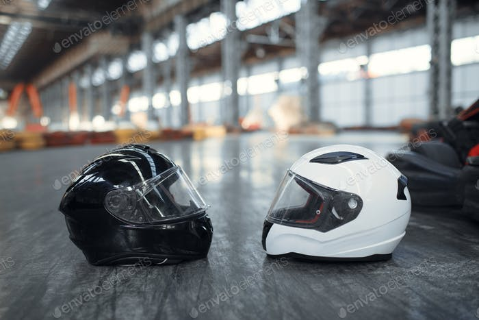 Two go kart helmets on the ground, karting