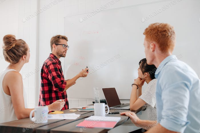 Executive explaining business plans to his coworkers