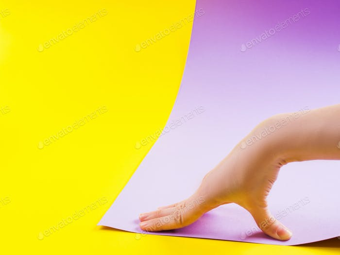 Female hand as snail on paper yellow and purple