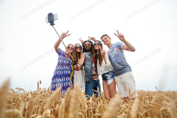 hippie friends with smartphone on selfie stick