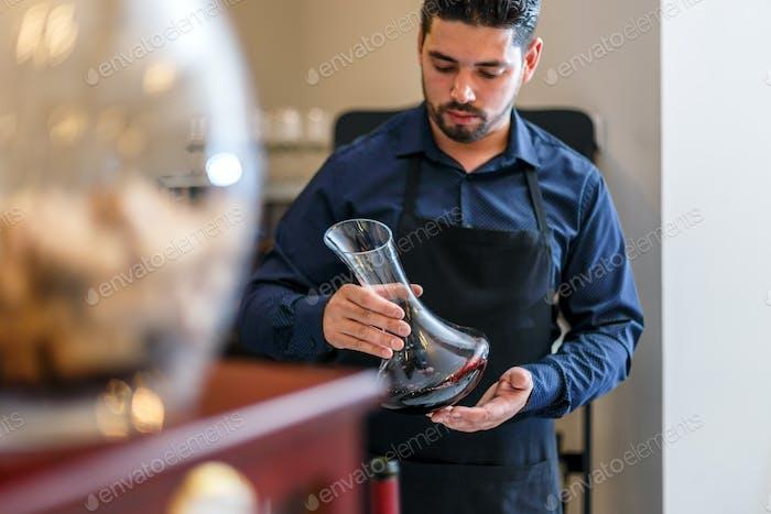 Waiter hold bottle of red wine