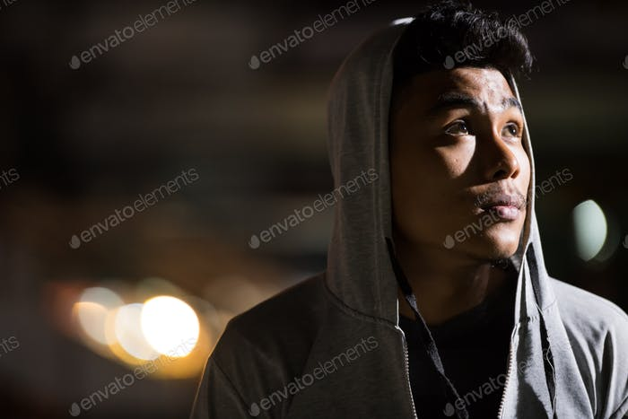 Face of young Asian man with hoodie thinking in the city streets at night