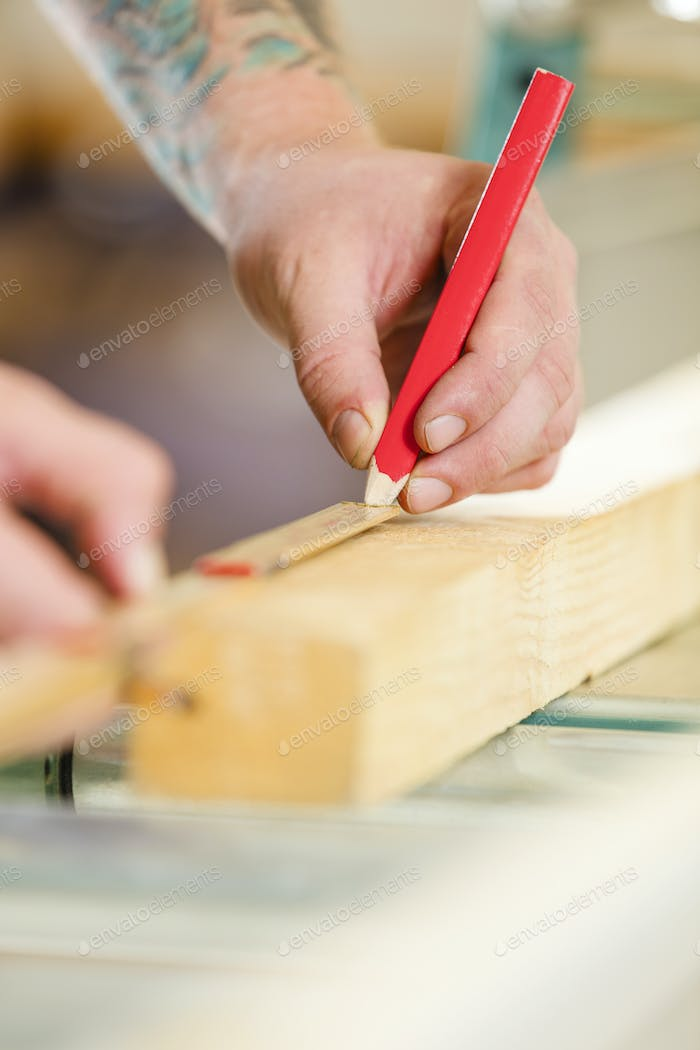 Carpenter measures the length of a wood plank before sawing