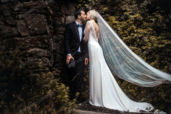 Lovely couple - bride and groom hugging and kiss in a beautiful mystery forest.