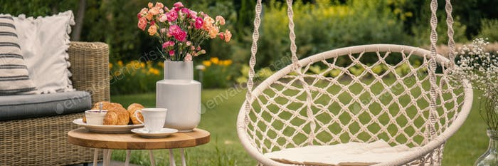 Flowers on table between hanging chair and rattan settee in the