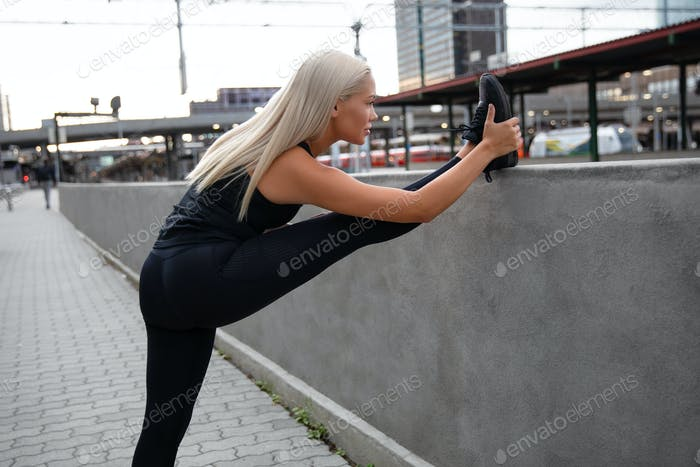 Pretty Woman Doing Stretching Exercise At Sidewalk Railing