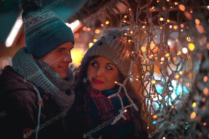 Paar in warmer Kleidung genießt colorul Weihnachtsmarkt, Bokeh Lichter Hintergrund