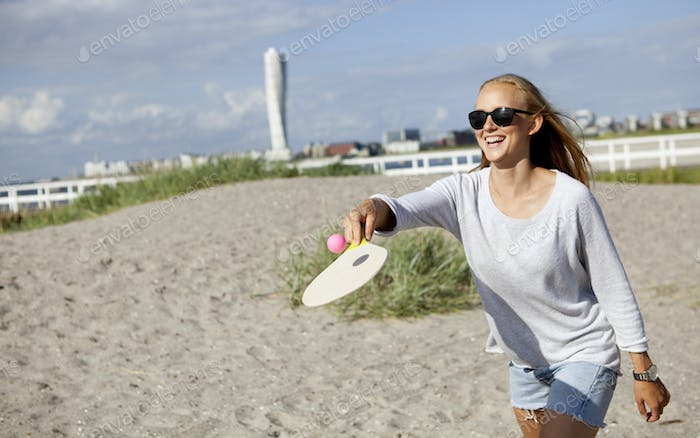 Happy woman playing tennis at beach against sky