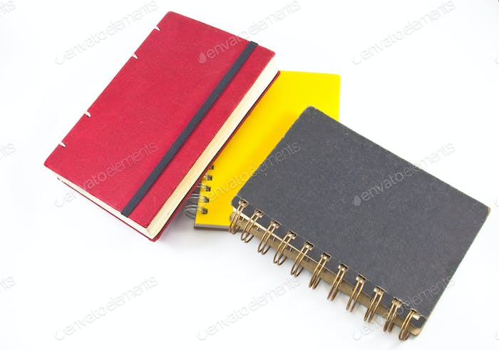 black,red and yellow notebooks closed isolated over white. Book