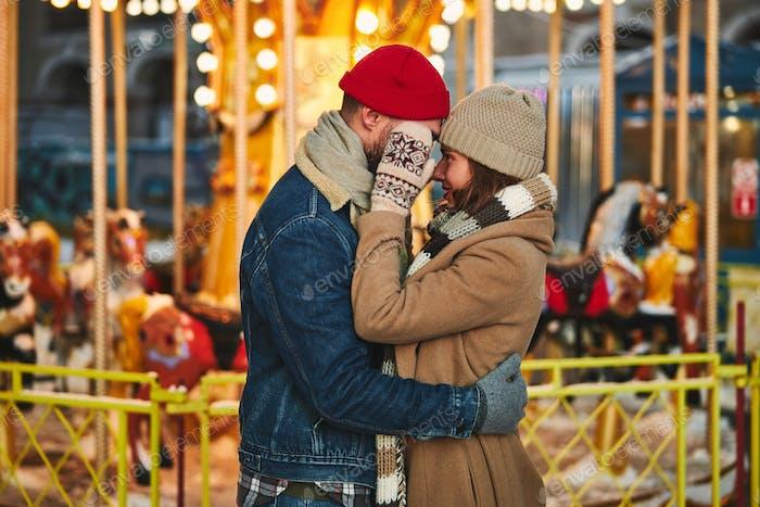 Feliz pareja cariñosa que sale en merry go round