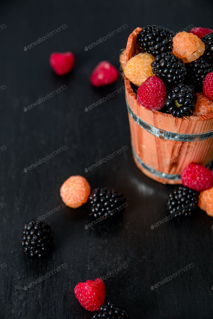 Mixed of red, black, yellow raspberries in a wooden basket and berry on  table. Close up.