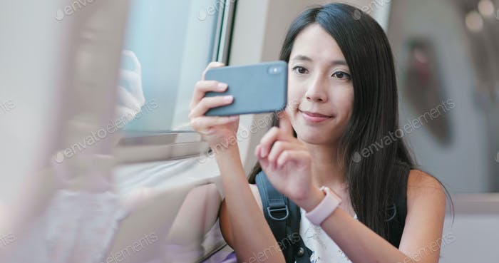 Happy woman visit taipei city and taking train, use of cellphone for taking video and photo