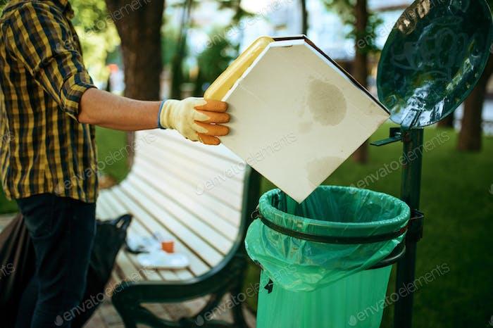Volunteer puts trash in plastic bag, volunteering