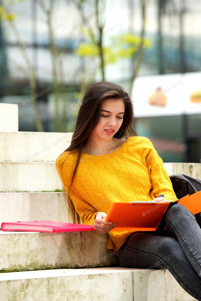 Attractive student sitting on steps studying