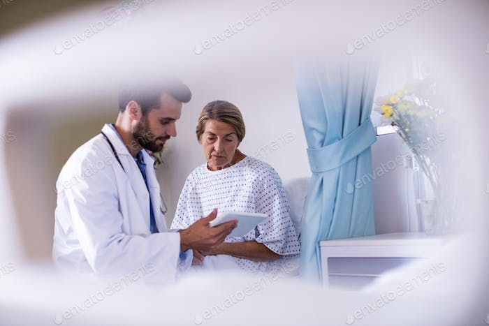 Male doctor showing digital tablet to female senior patient in the ward