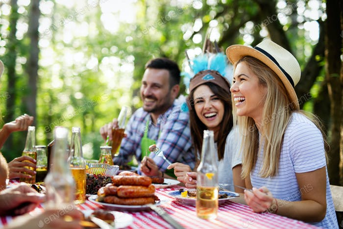 Happy friends enjoying barbecue and grill party outdoor