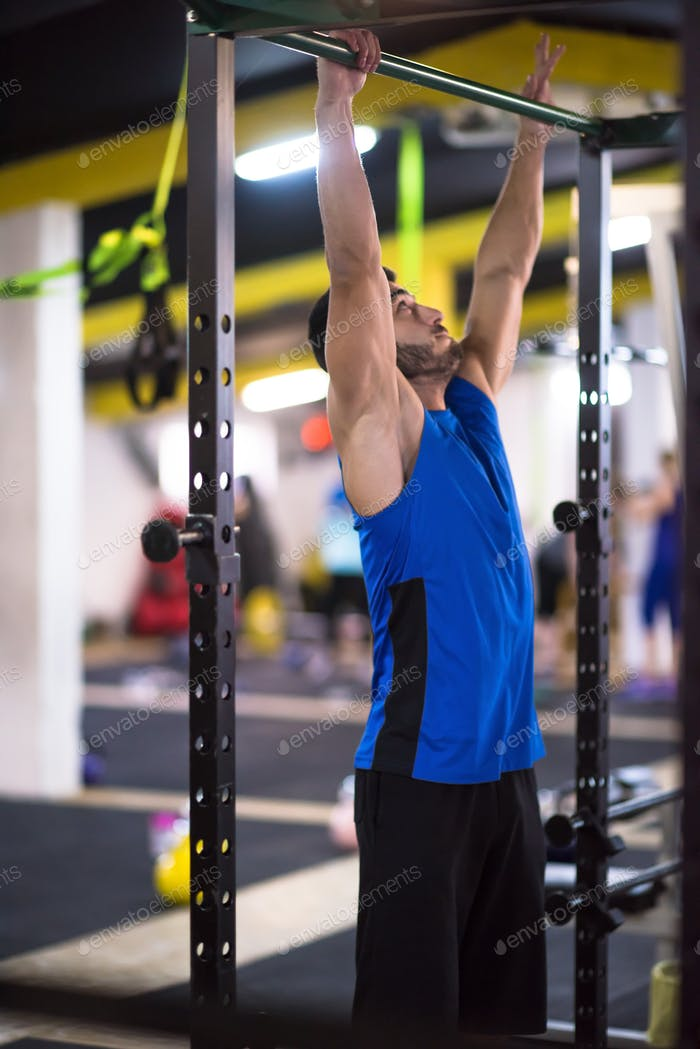 man doing pull ups on the horizontal bar