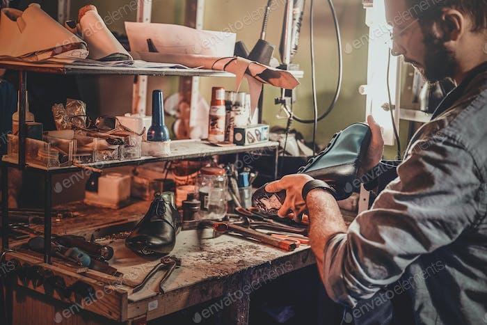 Кобблер ремонтирует обувь для клиентов
