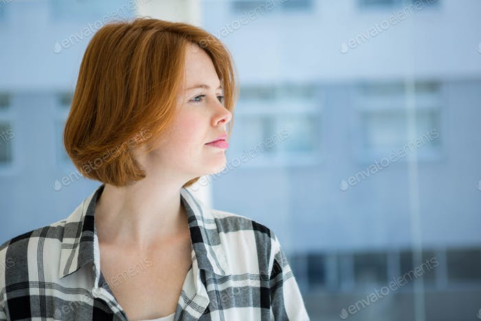 Red haired hipster smiling at camera in front of a window