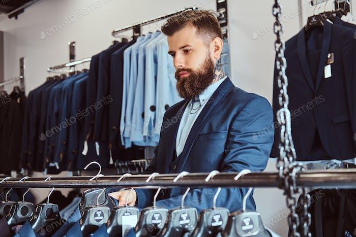 Татуированный мужчина со стильной бородой и волосами, одетыми в элегантный костюм, стоящий в магазине мужской одежды