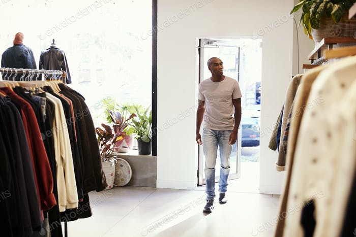 Young black man walking into a clothes shop