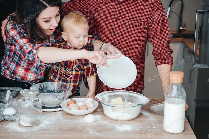 Mama fügt Butter zu Mehl hinzu