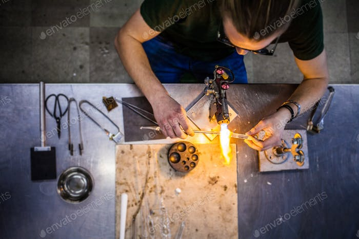 Glassblowing Young Man Working on a Torch Flame with Glass Tubes