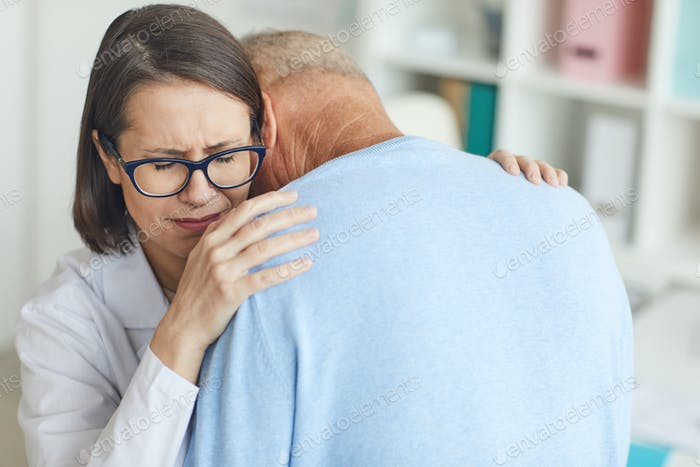 Female Doctor Embracing Crying Senior Man