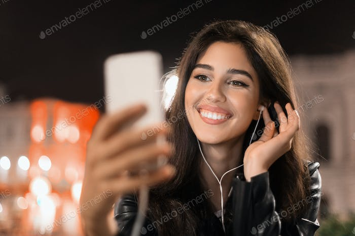 Woman making video-call on smartphone in night city