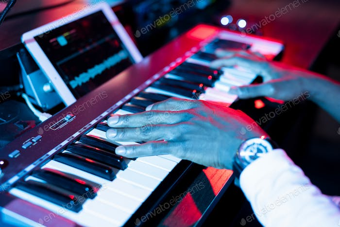 Hands of young contemporary musician over keys of pianoboard during making music