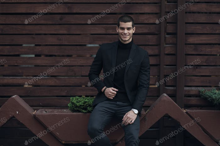Fashionable man, wearing a suit, sitting against the wooden wall