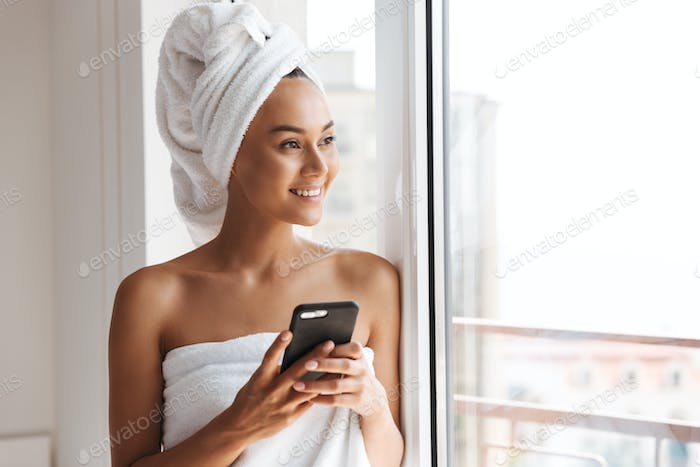 Cheerful young asian woman wrapped in a shower towel