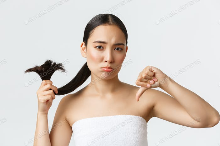 Beauty, hair loss products and hair care concept. Close-up of disappointed gloomy asian girl in bath