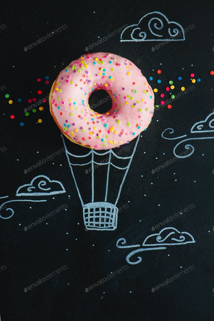 Pink glazed donut with chalk drawing of hot air balloon. Creative concept. Low key food photography.