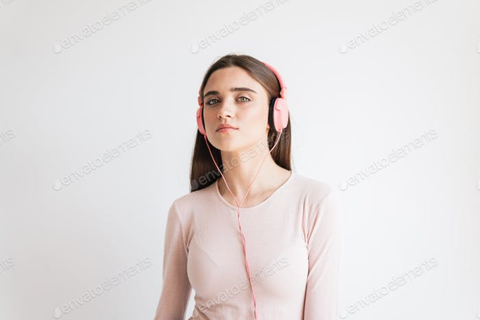 Portrait of a pretty young brunette girl listening to music