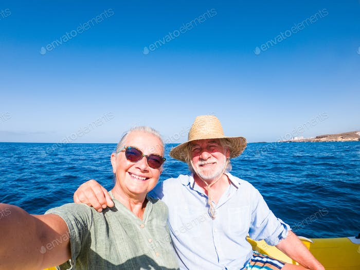 Beautiful and cute couple of seniors or old people in the middle of the sea driving