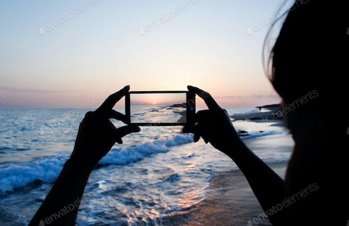 Девушка делает закат фото на телефоне