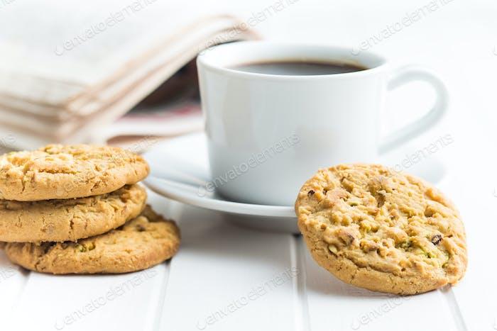 Süße Pistazienplätzchen und Kaffeebecher.