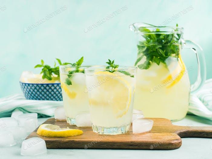 Fresh lemon lemonade in jug and glasses