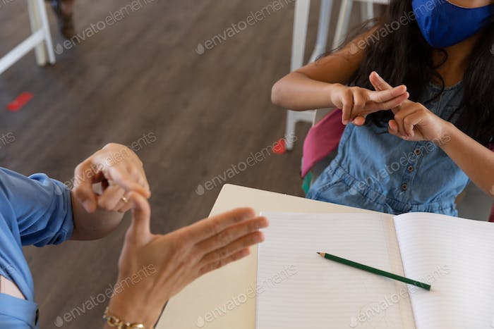 Mid section of female teacher and girl talking to each other through sign language in class