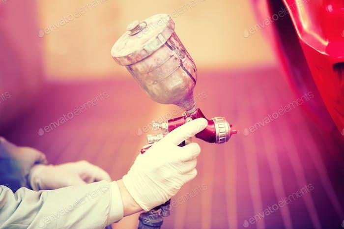 Arbeiter malen ein rotes Auto in Paiting Kabine mit professionellen Werkzeugen