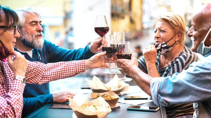 Senior couples toasting red wine at restaurant bar with face masks