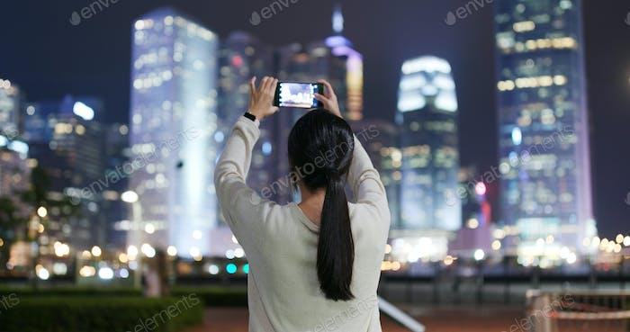 Frau fotografieren auf Handy in Hong Kong in der Nacht