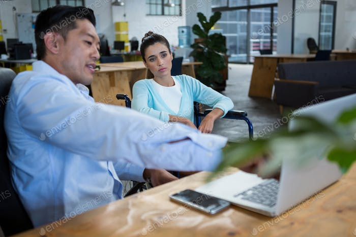 Businessman and disabled woman discussing over laptop