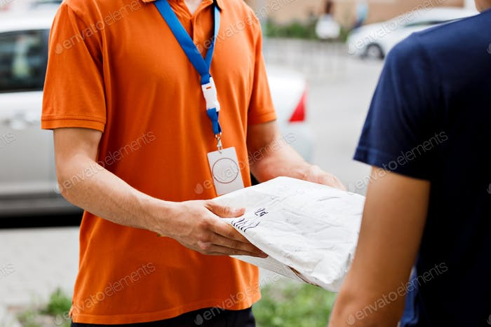 A person wearing an orange T-shirt and a name tag is delivering a parcel to a client. Friendly