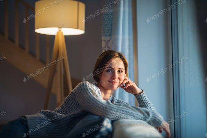 A young woman sitting indoors on a sofa at home, looking at camera.