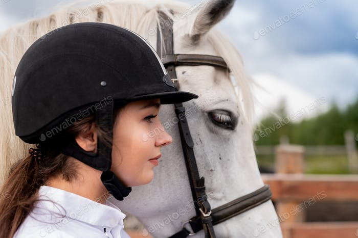 Profile of young active woman in equestrian helmet and white purebred horse