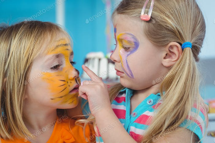 Smiling girls with their faces painted at the birthday party